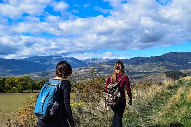 Dívky jdoucí v horské krajině-turistika