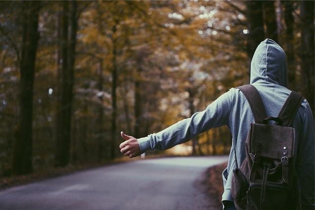 muž v mikině stojící u cesty