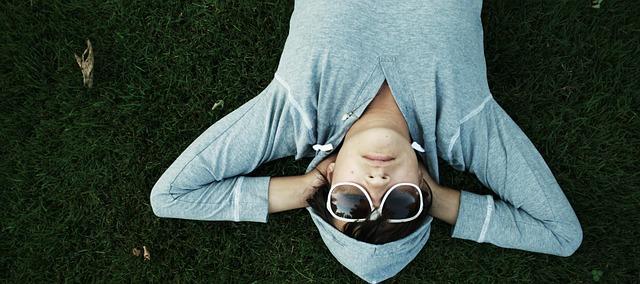 kluk ležící v trávě a v mikině
