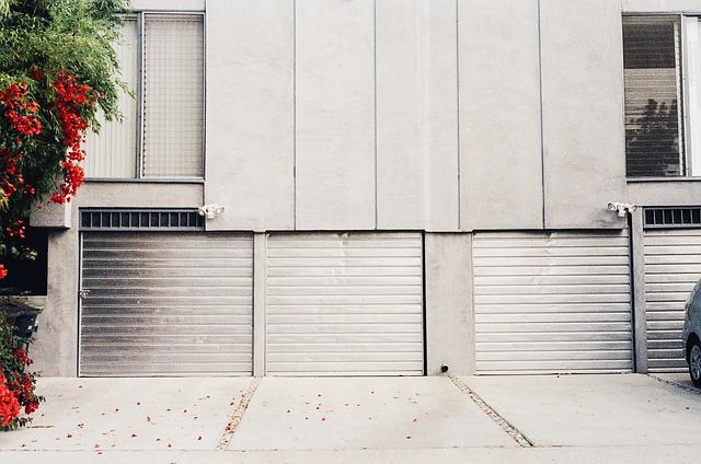 garážová vrata u bílého panelového domu